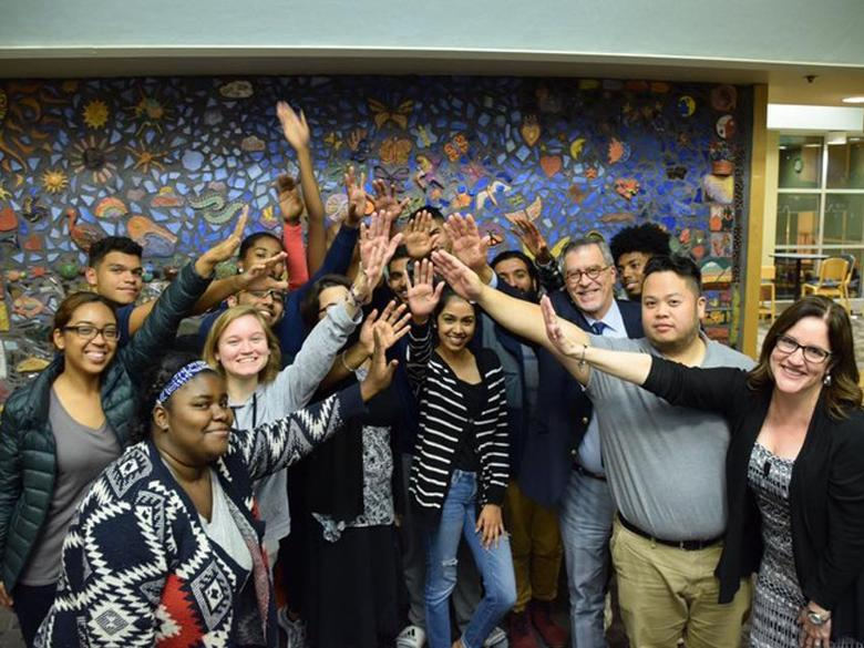 Group of students, faculty and staff from Penn State Abington raising their hands together.
